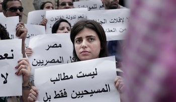A woman holds a sign reading, 'the demands are not only for Christians but for all Egyptians,' during a protest against a surge of assaults on Christians, Cairo, Egypt, August 13, 2016.