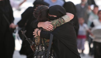 A woman embraces a Syria Democratic Forces fighter after she was evacuated with others from an ISIS-controlled neighborhood of Manbij, Syria, August 12, 2016.