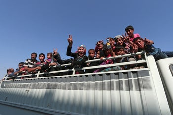 Civilians react atop of a pick-up truck after they were evacuated by the Syria Democratic Forces from an ISIS-controlled neighbourhood of Manbij, Syria, August 12, 2016.