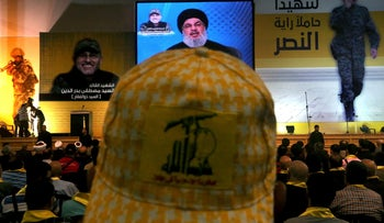 "A Hezbollah supporter wears a hat with Hezbollah flag, as he listens to Hassan Nasrallah, in a southern suburb of Beirut, Lebanon. May 20, 2016. The Arabic words on the right read:""A martyr holds the victory ensign."""