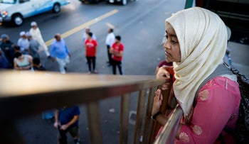 A young woman looks over the area crime scene in which imama and another man were shot dead in New York. Aug. 13, 2016,