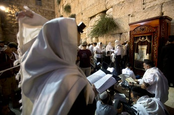 Ultra-Orthodox Jewish men pray during the mourning ritual of Tisha B'Av at the Western Wall in Jerusalem's Old City on August 14, 2016.