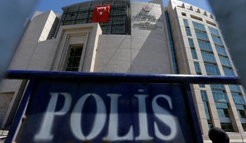 A woman enters a courthouse as a police fence is on display outside the building in Istanbul, on Monday, Aug. 15, 2016.