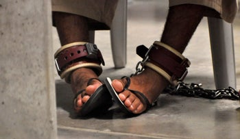 "In this photo, reviewed by a U.S. Department of Defense official, a Guantanamo detainee's feet are shackled as he attends a ""Life Skills"" class at Guantanamo Bay U.S. Naval Base April 27, 2010."