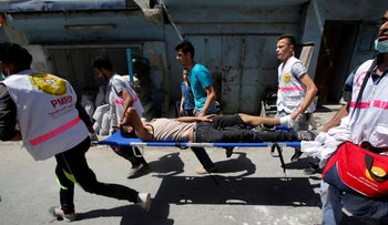 Medics carry an injured Palestinian during clashes with Israeli troops in the West Bank Al-Fawwar refugee camp, south of Hebron August 16, 2016.