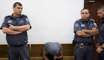 The suspect in the rape at Tel Aviv's Allenby 40 club at a detention hearing, August 17, 2016. A young man sits on a bench, bent over and with a shirt over his head to conceal his face.