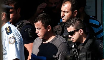 A Turkish military officer is escorted by policemen as he leaves a building of the Greek Asylum Service in Athens, Greece, July 27, 2016.