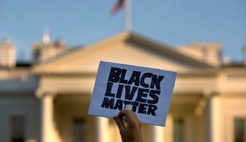 """A man holds up a sign saying """"black lives matter"""" during a protest of shootings by police, at the White House in Washington. July 8, 2016."""