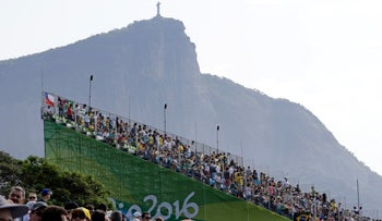 The statue of Christ the Redeemer on Mount Corcovado and a crowd at the Rio Olympics, August 18, 2016.