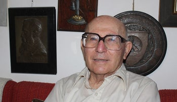 Shaul Ladany in his Be'er Sheva home with a prized piece of his Theodor Herzl collection (left), August 2016.