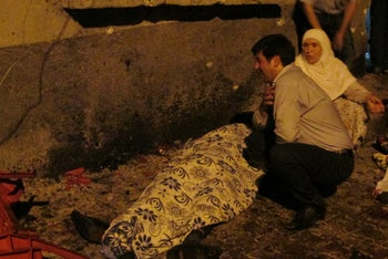 A man and a woman mourn next to a body of one the victims of a blast targeting a wedding ceremony in the southern Turkish city of Gaziantep, Turkey, August 20, 2016.