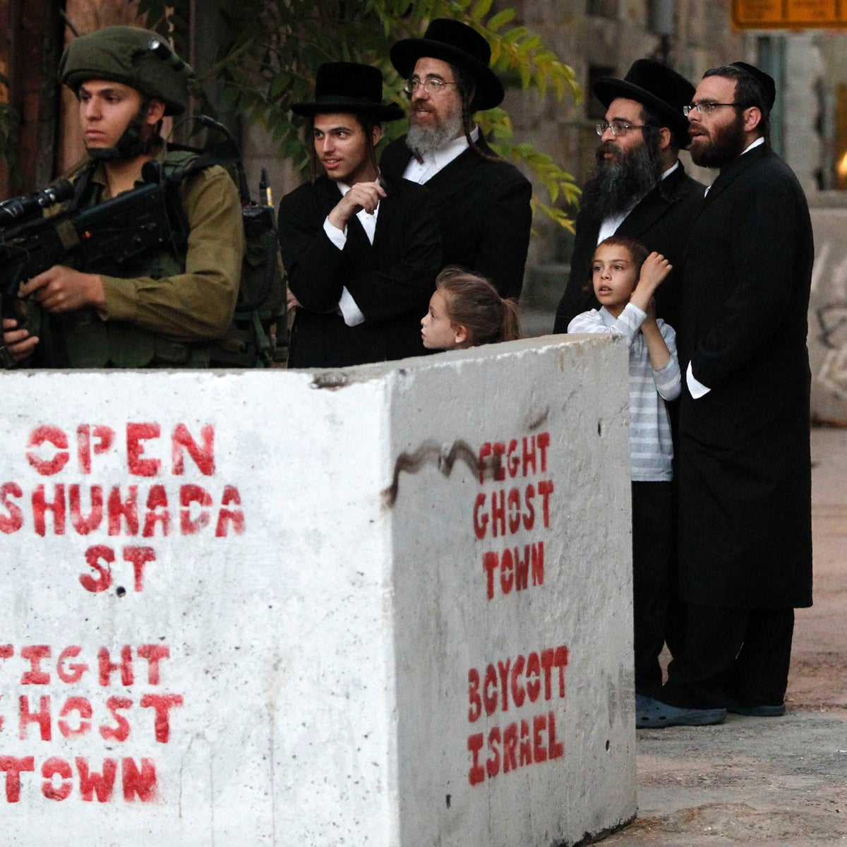 """Ultra-Orthodox Jewish men stand behind a roadblock on which a graffiti reads """"open Shuhada street"""" in a Palestinian neighborhood in Hebron. August 14,2016."""
