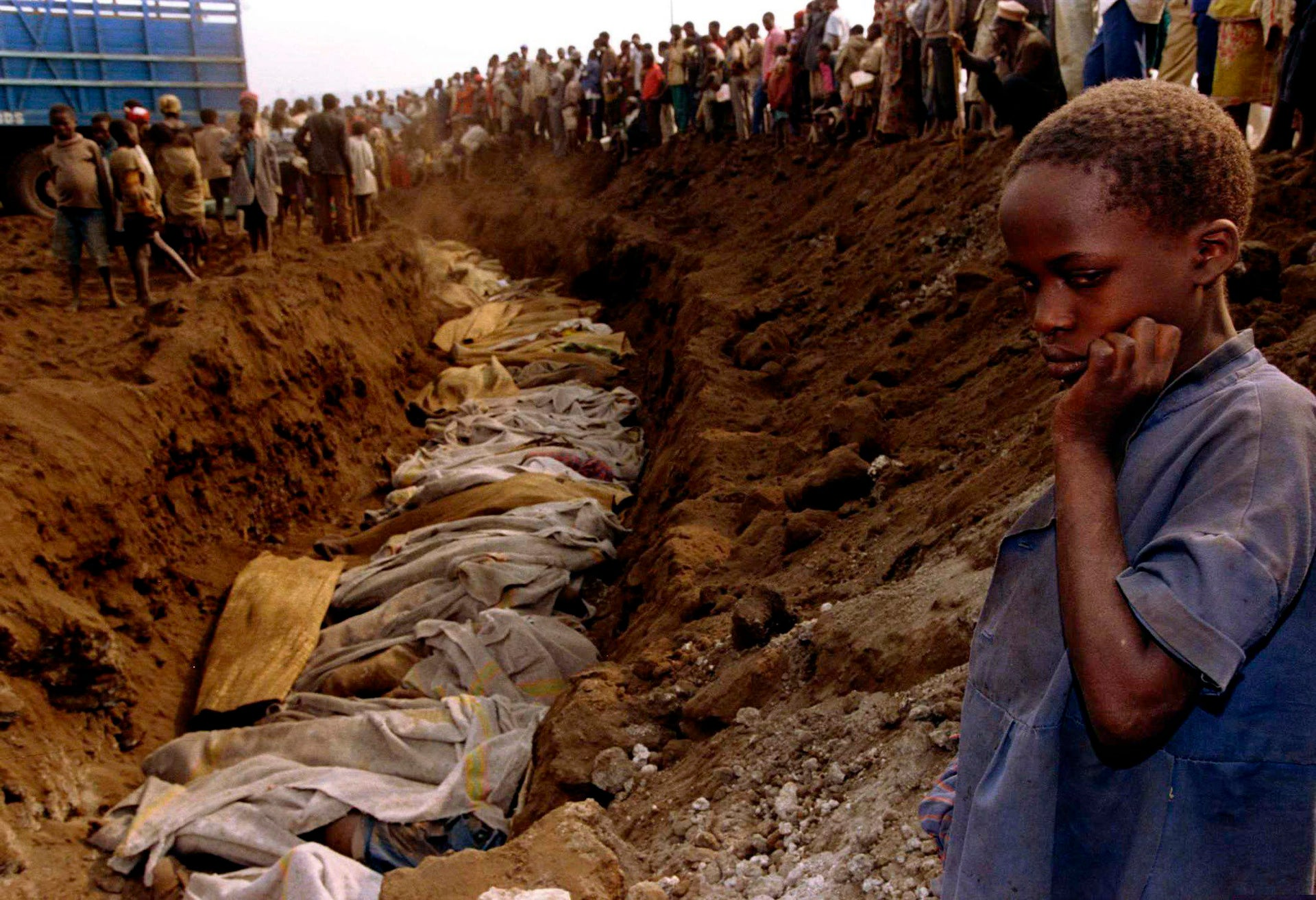 A Rwandan refugee girl stares at a mass grave where dozens of bodies have been laid to rest, July 20, 1994.