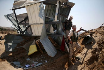 Palestinian security officers survey damage done by an Israeli air strike on a Hamas target in Gaza on August 22, 2016.