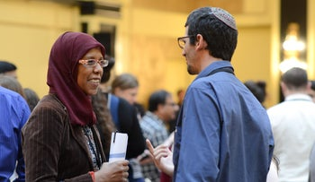 A Muslim woman and a Jewish man speak at the seventh Muslim Jewish Conference in Berlin, Germany, August 2016.