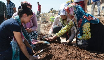Women kneel by a grave during the funeral for the victims of an attack on a wedding party that left 50 dead in Gaziantep, Turkey, August 21, 2016.