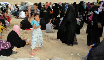 Internally displaced civilians from Fallujah, who fled their homes during fighting between Iraqi security forces and Islamic State group, arrive to a camp outside Fallujah, Iraq, Monday, June 20, 2016.