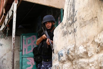 A member of the Palestinian security forces takes position behind a wall in the West Bank city of Nablus on August19 during ongoing clashes between the security forces and Palestinian gunmen.