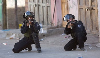 Israeli security forces aim their weapons during clashes in the refugee camp of Al-Fawwar, near the West Bank city of Hebron, Aug. 16, 2016.