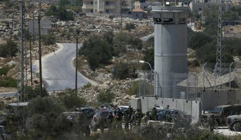 Israeli soldiers gather at the scene where a suspected Palestinian man was shot dead by Israeli troops at the entrance to the West Bank village of Silwad on August 26, 2016.