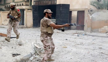 A memebr of the forces loyal to Libya's UN-backed Government of National Accord (GNA) lays down cover fire as a fellow member runs on August 28, 2016, in the coastal city of Sirte.