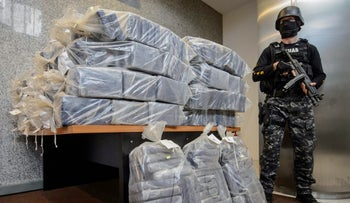 An armed policeman stands next to packs of cocaine at the organized crime prosecutor' office in Bucharest, Romania, July 1, 2016.