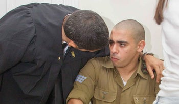 Israel Defense Forces soldier Elor Azaria, the so-called Hebron shooter, with his lawyer in the courtroom in Jaffa, on Aug. 28, 2016.