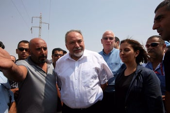 Defense Minister Avigdor Lieberman, center, with ministers Uri Ariel and Gila Gamliel, during a tour of Bedouin settlements in the Negev on August 29, 2016.