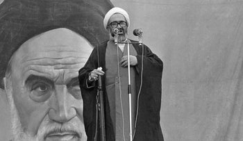 President of Iran's Ruling Revolutionary Council, Ayatollah Hossein Ali Montazeri holds a rifle as he addresses a large rally at Tehran University, November 1979.