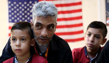 In this photo taken Sunday, August 28, 2016, Syrian refugee Nadim Fawzi Jouriyeh, 49, speaks to reporters at the Amman, Jordan office of the International Organization for Migration. Jouriyeh is flanked by his sons Farouq, 8, and Hamzeh, 12.
