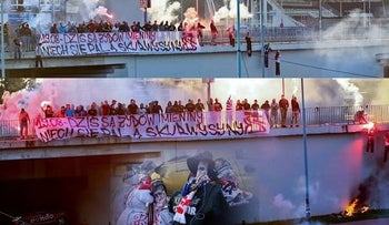 The fans, some wearing balaclavas, set fire to at least three puppets hanging from the bridge and are understood to symbolize burning Jews.