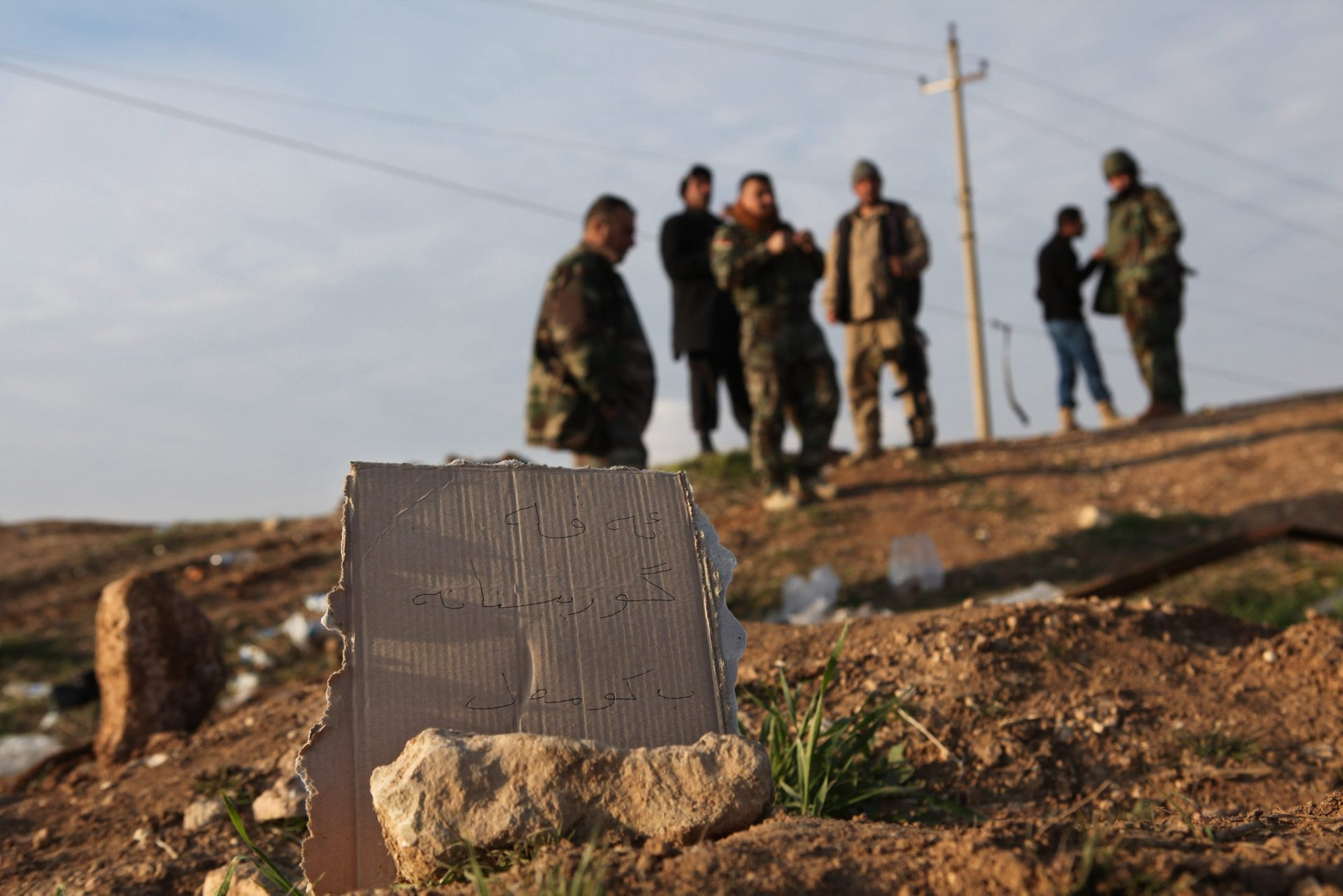 "In this Dec. 22, 2014, file photo, Kurdish Peshmerga forces inspect a site marked in Kurdish with a sign reading, ""Kurdish mass grave,"" in Hardan village in northern Iraq."