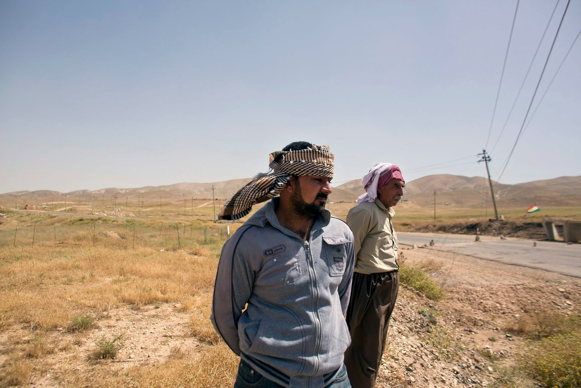 In this May 19, 2016 photo, Arkan Qassim, center, stands at the site where he witnessed the killing dozens of Yazidi men including two sons of Rasho Qassim, right.