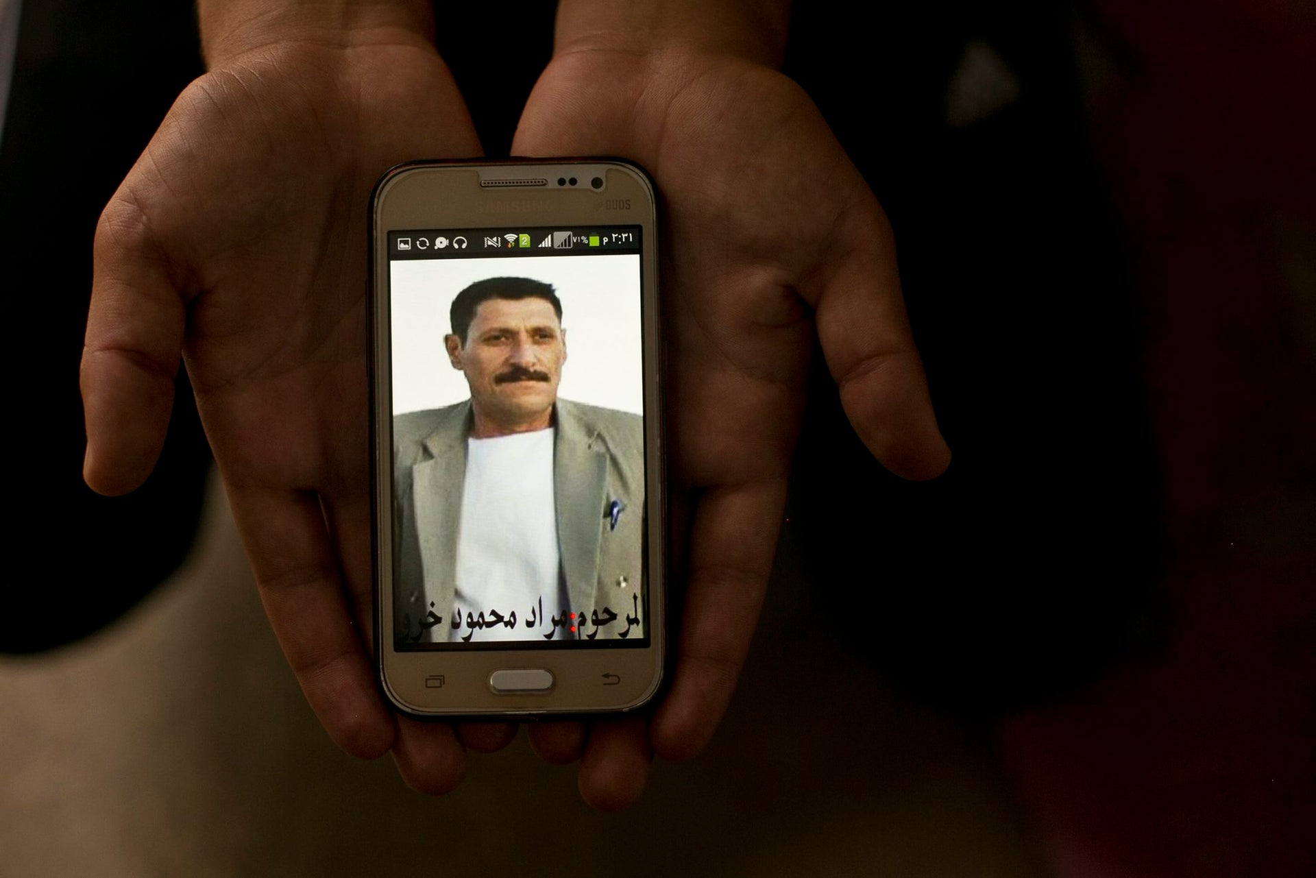 In this May 18, 2016 photo, a relative shows a phone picture of Mahmoud Murat during an interview with AP at Kankhe Camp for the internally displaced in Dahuk, northern Iraq.