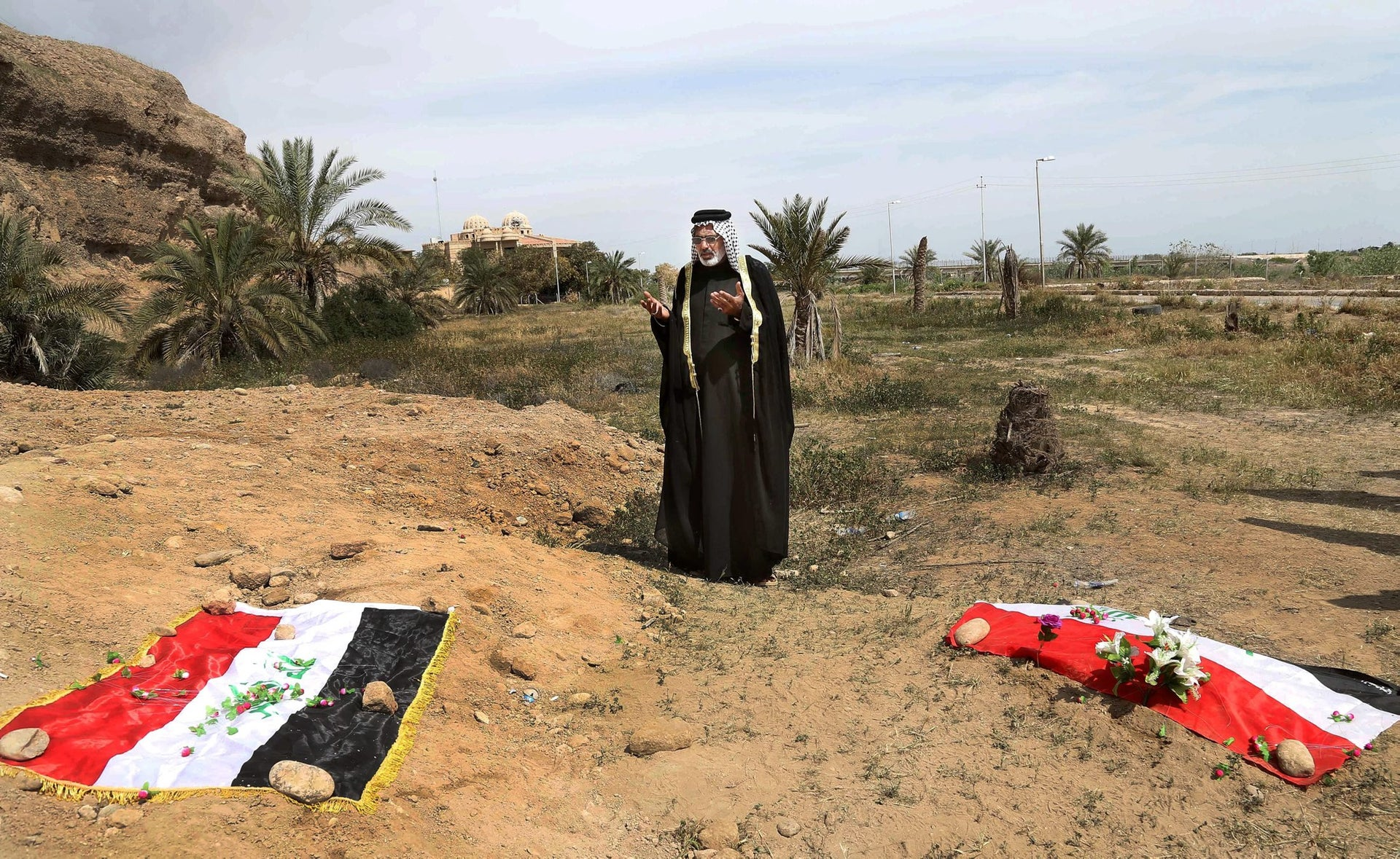 In this April 3, 2015, file photo, a man prays for his relative at the site of a mass grave believed to contain the bodies of soldiers killed by ISIS when it overran Camp Speicher military base in Tikrit, Iraq.