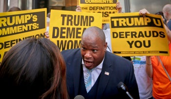 Donald Trump supporter Mark Burns, an evangelical pastor from South Carolina, is surrounded by vocal anti-Trump protesters on Thursday Aug. 25, 2016, in New York.
