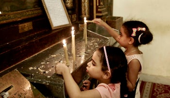 Egyptian Christian girls light candles in the Hanging Church in Old Cairo, Egypt, August 30, 2016.