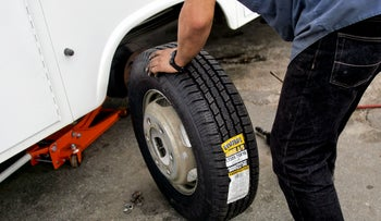 Robert Hernandez installs a new tire on a pick-up truck at Rockside Tire Sales & Services in Garner, North Carolina, U.S., on Wednesday, Sept. 2, 2009.