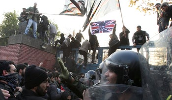 Iranian police officers prevent further protesters from entering the British Embassy, as others stand on the gates holding a satirized British flag and Islamic flags, in Tehran, Iran, Tuesday, Nov. 29, 2011.