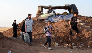 Syrian families, fleeing ISIS and the ongoing fighting, carry their belongings as they arrive to take refuge in the rebel-held village of al-Khalfatli, Syria, August 29, 2016.