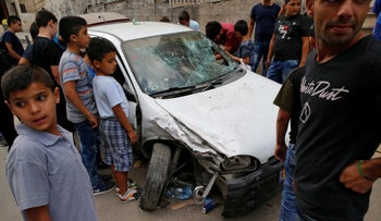Palestinians surround the car of Mustafa Nimer, who Israeli police initially said attempted to ram policemen and was consequently shot and killed in Shoafat near Jerusalem September 5, 2016.