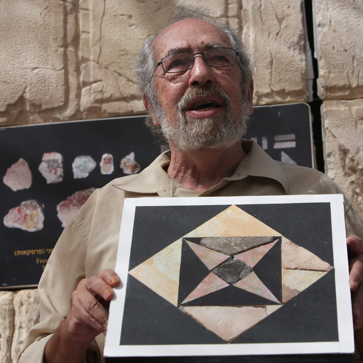 Dr. Gabriel Barkay from the City of David Foundation shows a restored tile during a press conference on September 6, 2016 in the Emek Tzurim National Park located near Mount Scopus in Israeli-annexed east Jerusalem.