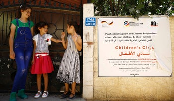 Palestinian girls stand at the entrance of a project by the Christian charity World Vision, in Beit Lahia, Gaza Strip, August, 16 2016.