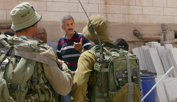 Aref Jaber speaks to Israeli soldiers outside his home in Hebron.