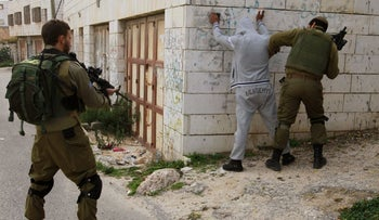 Israel Defense Forces soldiers searching a Palestinian in Hebron, December 2015.