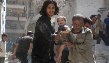 A Syrian civil defense member and a volunteer carry a little girl rescued from under the rubble of destroyed buildings following a reported airstrike on Aleppo. September 10, 2016.