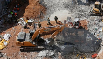 Rescue workers attempt to locate the two missing persons in the rubble of the collapsed parking lot in north Tel Aviv, September 9, 2016.