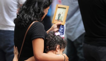 A young girl holds her mother during a commemoration ceremony for the victims of the September 11 terrorist attacks at the National September 11 Memorial and Museum fifteen years after the day on September 11, 2016 in New York City.