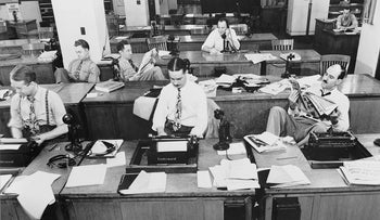 The Newsroom of the New York Times newspaper in 1942. Reporters and rewrite men wrote stories and waited to be sent out. Rewrite man in background gets the story on the phone from reporter outside.