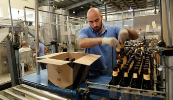 Carakale Brewery staffer Ramzi Kharoufeh fills a box with beer bottled, pasteurized and labeled at the Jordanian factory, on September 6, 2016.